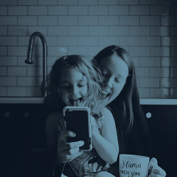 A mom and daughter laughing at something on a mobile device